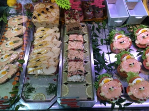 Slices of terrines, pâtés, and salmon in pastry at a Paris traiteur.