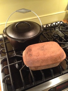 A cast iron Dutch oven (rear) and a clay baker (front). Both are great for giving loaves a super-crispy, light crust.