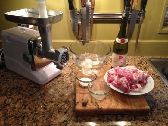 On the cutting board, going clockwise from 1pm: red wine, pork shoulder, pepper, thyme, nutmeg, salt, hog casings.